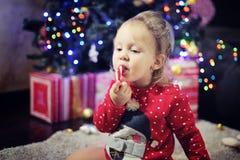 Niña linda que come el bastón de caramelo de la Navidad Imagen de archivo
