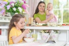Niña linda que come la ensalada fresca en la tabla de cocina Foto de archivo