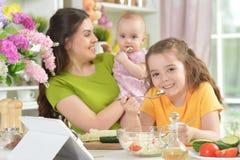 Niña linda que come la ensalada fresca en la tabla de cocina Imagen de archivo