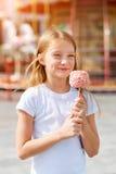 Niña linda que come la manzana de caramelo en la feria en parque de atracciones Fotos de archivo