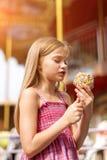 Niña linda que come la manzana de caramelo en la feria en parque de atracciones Imagen de archivo libre de regalías