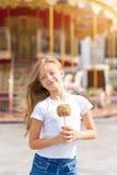 Niña linda que come la manzana de caramelo y que presenta en la feria en parque de atracciones Foto de archivo