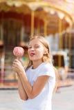 Niña linda que come la manzana de caramelo y que presenta en la feria en parque de atracciones Imagenes de archivo
