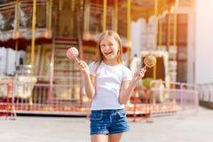 Niña linda que come la manzana de caramelo y que presenta en la feria en parque de atracciones Imagen de archivo libre de regalías