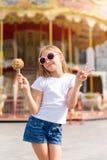 Niña linda que come la manzana de caramelo y que presenta en la feria en parque de atracciones Fotografía de archivo libre de regalías