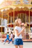 Niña linda que come la manzana de caramelo y que presenta en la feria en parque de atracciones Imágenes de archivo libres de regalías