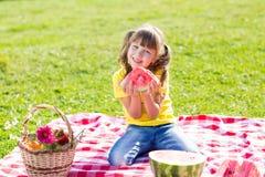 Niña linda que come la sandía en hierba adentro Fotos de archivo