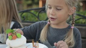 Niña linda que come la torta en el café del aire abierto almacen de metraje de vídeo