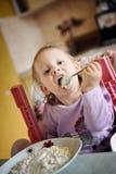 Niña linda que come las gachas de avena Imagen de archivo