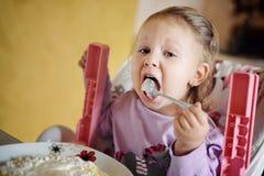 Niña linda que come las gachas de avena Fotografía de archivo