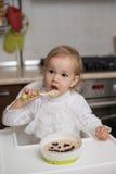 Niña linda que come las gachas de avena sanas Foto de archivo libre de regalías