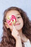 Niña linda que come una piruleta Foto de archivo libre de regalías