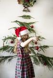 Niña linda que cuelga para arriba los ornamentos de la Navidad fotos de archivo