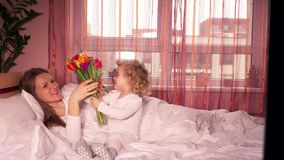 Niña linda que da las flores a la mamá en cama el día del ` s de la madre almacen de video