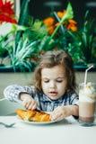 Niña linda que desayuna con el cruasán en un restaurante Imagen de archivo libre de regalías