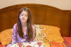 Niña linda que despierta en su cama Bostezo soñoliento del niño en cama Pequeño soñoliento imagen de archivo