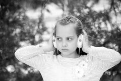 Niña linda que disfruta de música usando los auriculares fotografía de archivo