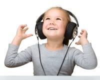 Niña linda que disfruta de música usando los auriculares Foto de archivo libre de regalías