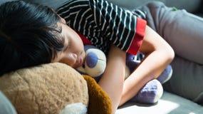 Niña linda que duerme con el oso de peluche Foto de archivo