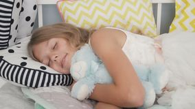 Niña linda que duerme con el oso de peluche en cama en casa almacen de metraje de vídeo