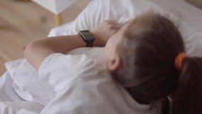 Niña linda que duerme en la cama en casa Muchacha adorable que despierta de un despertador en su reloj elegante moderno almacen de video