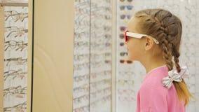 Niña linda que elige las gafas de sol de la exhibición en la alameda de compras almacen de metraje de vídeo