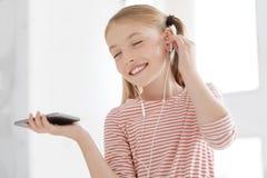 Niña linda que escucha su álbum preferido de la música foto de archivo