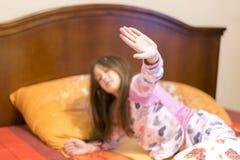 Niña linda que estira sus brazos feliz con una sonrisa de despertar en su cama Bostezo soñoliento del niño en cama Pequeño soñoli imagen de archivo libre de regalías