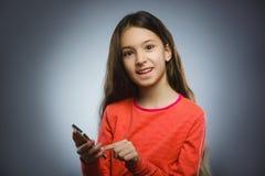 Niña linda que habla en el teléfono celular Aislado en gris imagen de archivo libre de regalías