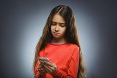 Niña linda que habla en el teléfono celular Aislado en gris imágenes de archivo libres de regalías