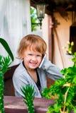 Niña linda que habla en el teléfono Niño con el móvil, sonriendo Mirada de la cámara Foto de archivo