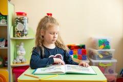 Niña linda que hace la preparación, leyendo un libro, páginas que colorean, una escritura y una pintura enseñanza en guardería foto de archivo libre de regalías