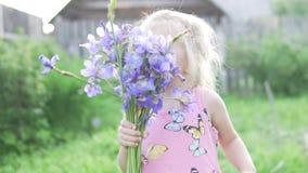 Niña linda que huele un ramo de iris azules metrajes