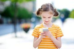 Niña linda que juega al juego móvil al aire libre en su teléfono elegante Fotografía de archivo
