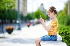 Niña linda que juega al juego móvil al aire libre en su teléfono elegante Imagenes de archivo