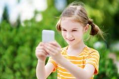 Niña linda que juega al juego móvil al aire libre en su teléfono elegante Fotografía de archivo libre de regalías