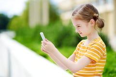 Niña linda que juega al juego móvil al aire libre en su teléfono elegante Fotos de archivo libres de regalías