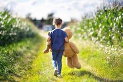Niña linda que juega con dos peluches del juguete del empuje Embrome sostener el oso enorme y el pequeño oso y caminar en paisaje Imagen de archivo libre de regalías