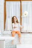 Niña linda que juega con el rollo del papel higiénico Foto de archivo