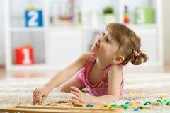 Niña linda que juega con los bloques educativos del juguete en un cuarto soleado de la guardería Cabritos con la tarjeta Niños en Imagen de archivo libre de regalías