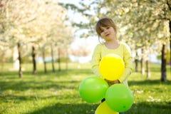 Niña linda que juega con los globos en un manzano floreciente Imagenes de archivo