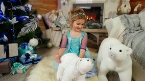Niña linda que juega con los juguetes en la casa, el niño que juega cerca del árbol de navidad, ` s Eve, la Navidad del Año Nuevo almacen de metraje de vídeo