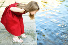 Niña linda que juega con una fuente de la ciudad en día de verano caliente y soleado Fotos de archivo