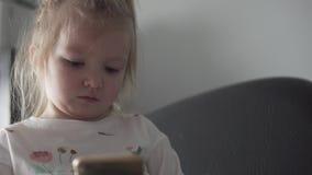 Niña linda que juega el teléfono móvil almacen de metraje de vídeo