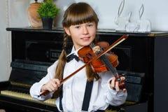 Niña linda que juega el violín y el ejercicio Imagen de archivo