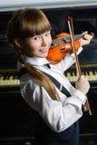 Niña linda que juega el violín y el ejercicio Foto de archivo