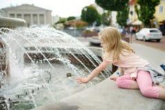 Niña linda que juega por la fuente de la ciudad en día de verano caliente y soleado Niño que se divierte con agua en verano imagen de archivo