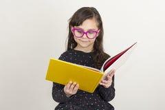 Niña linda que lee un libro fotos de archivo