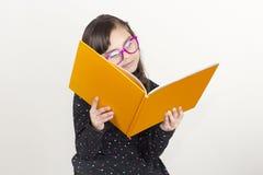 Niña linda que lee un libro imagenes de archivo