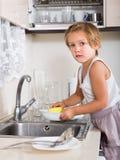 Niña linda que limpia platos sucios Fotos de archivo libres de regalías